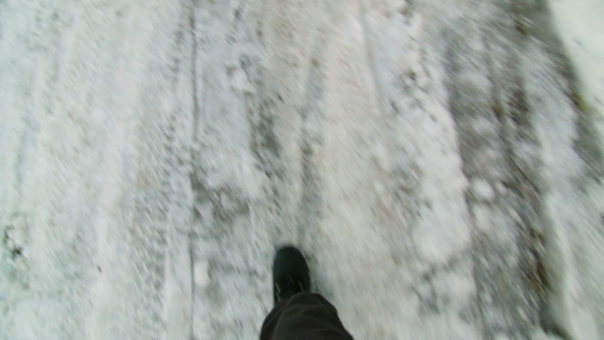 Walking POV Looking Down at feet of a Man on Icy Road