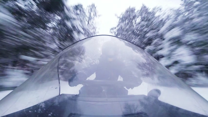 Fast Snowmobile Driver and Windshield Reflection in a Forest Path