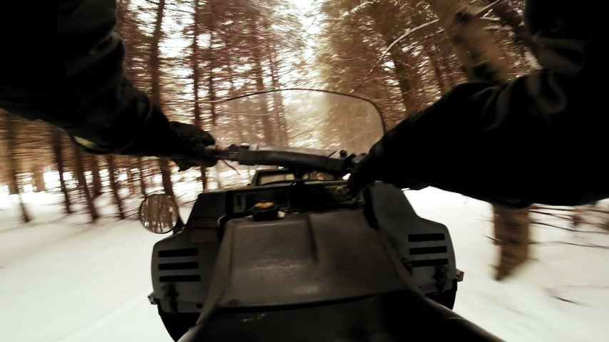 POV footage of Man Riding a Fast Snowmobile in Forest Stock Footage