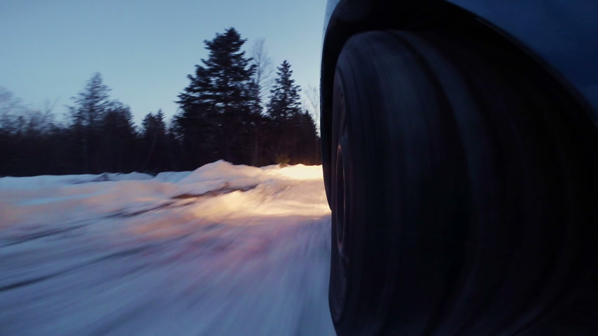 Closeup of a Rally Car Wheel Driving Off Road during Winter Sunset