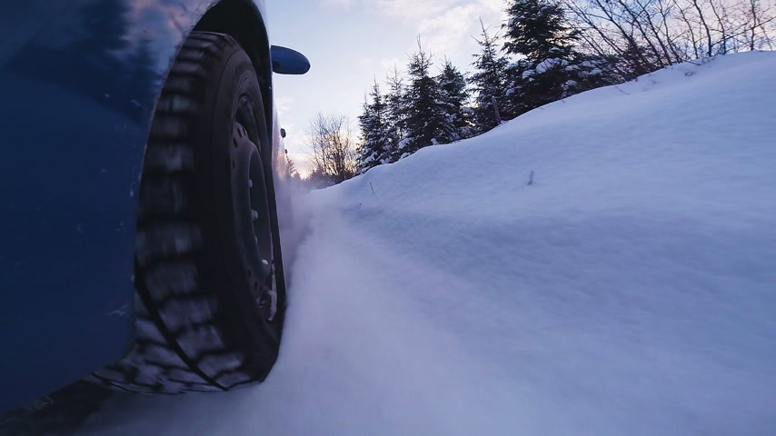 Back View Closeup of a Rally Car Wheel Driving Off Road during Winter Sunset Stock Footage
