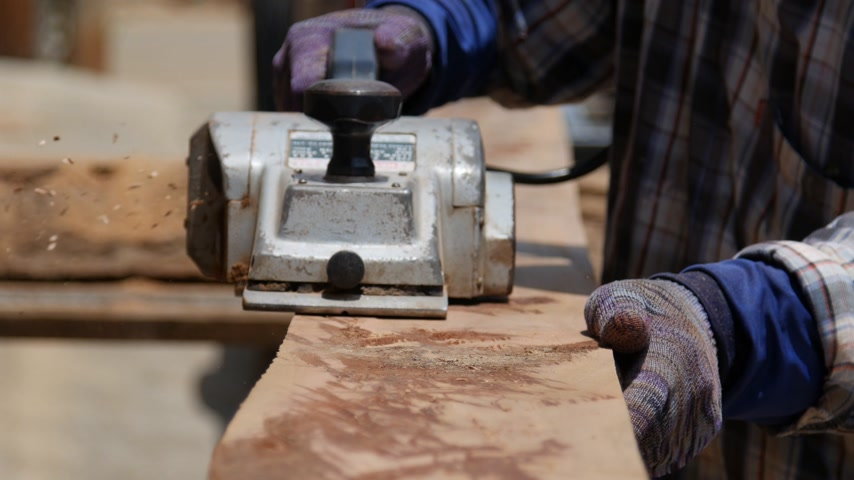 rendelenmiş : worker planing a plank of wood with a electric planed