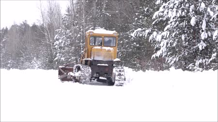 recentemente : Clearing snow from the road. Crawler Tractor grader clears snow from the road. The snow is fresh, it has dropped recently. Snow White, fluffy and beautiful. Road service road from the clean fresh snow. Around the beautiful snow-covered forest.