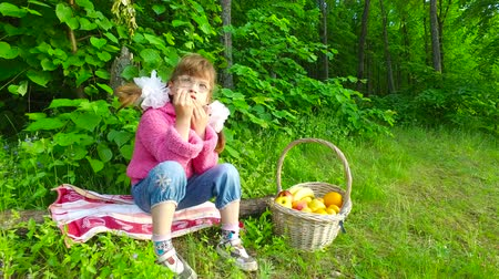 banany : Girl child eats apricots in summer forest. The girl has a good appetite in the fresh air. Fruits are very tasty. Summer evening in the forest. Wideo