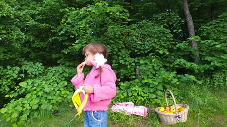 muz : Girl child eats banana in a summer forest. The girl has a good appetite in the fresh air. Fruits are very tasty. Summer evening in the forest.