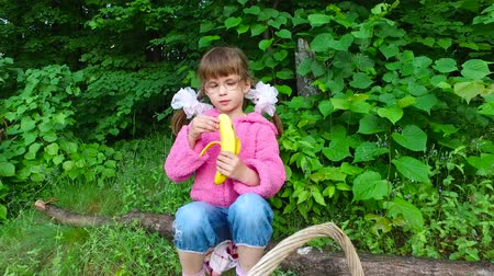 banany : Girl child eats banana in a summer forest. The girl has a good appetite in the fresh air. Fruits are very tasty. Summer evening in the forest.