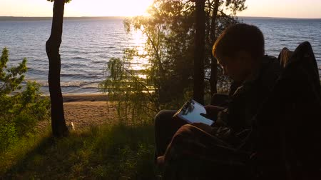tél : Boy teenager sitting on a chair on the shore of a large lake. Teen Boy enthusiastically playing a computer game on a Tablet PC. Boy teenager fascinated by the game and did not notice anything around. Sunny summer evening.