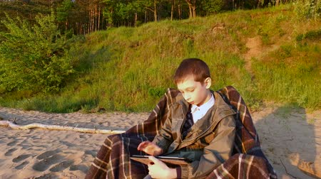 tél : Boy teenager sitting on a chair on the sandy ground. Teen Boy enthusiastically playing a computer game on a Tablet PC. Boy teenager fascinated by the game and did not notice anything around. A cold wind is blowing. Sunny summer evening.