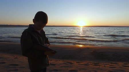 tél : Teen boy standing at the waters edge on the shores of a large lake. Teen Boy enthusiastically playing a computer game on a Tablet PC. Boy teenager fascinated by the game and did not notice anything around. Sunny summer evening.