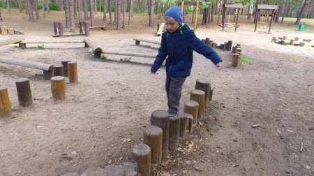 soft earth : Boy child blonde is engaged in the wooden logs. Little boy playing on the playground. A cloudy autumn day in the park. Stock Footage