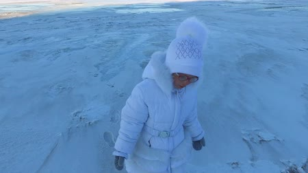 еще : Girl child leaves the frozen lake. The child goes home with disappointment. Girl would like to take a walk on the ice yet. Frosty winter day.