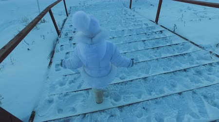 fur boots : Girl child goes down the stairs covered with snow. Child is walking in the park. Winter frosty day. Stock Footage
