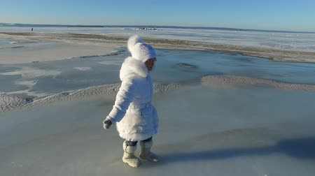 fur boots : Girl child walks on the ice large lake. Girl is glad that the lake was frozen. The child can now slide on the ice. Sunny frosty winter day.