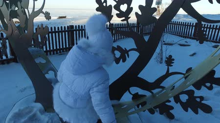 climbed : Girl child climbed on a metal tree. Child laughs and rejoices standing on an iron figure. Frosty winter day.