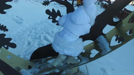 fur boots : Girl child climbed on a metal tree. Child laughs and rejoices standing on an iron figure. Frosty winter day.