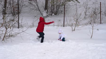 superb : Mother and daughter throw up soft, fresh snow. Woman and a girl child is rejoice winter. A cloudy winter day in the park. Slow motion.