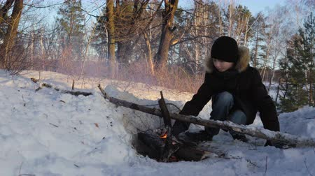 плохо : Teen boy lit a fire in the forest. The boy is heated from fire, in the woods cold. The fire burns badly, as the wood is wet. Sunny winter evening in the forest.