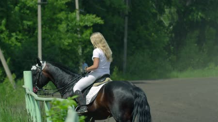 sela : A beautiful girl in white hair. The girl is finished training and goes to the recreation area. The girl is a little tired and sweat is on her face. Sunny summer day on a green glade. Vídeos