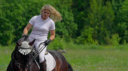 sela : SLOW MOTION: A beautiful girl in white hair and white clothes is riding a black brown stallion. The girl makes the horse perform various beautiful movements. The girls hair develops in the wind.
