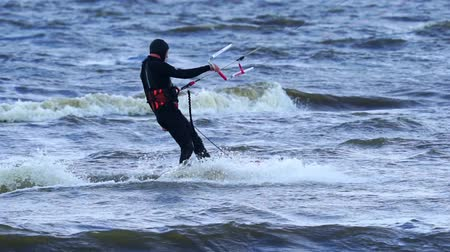 beautifully : SLOW MOTION: Middle aged man is engaged in kiting. He beautifully rides a kite on the waves of the lake. Strong wind blows. A man likes to practice kite in extreme weather. Active way of life at any age. Cold autumn weather.