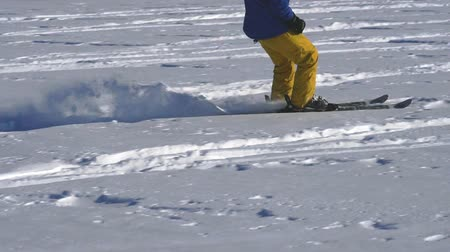 snowboard : SLOW MOTION: A male athlete is engaged in kiting on skis. He rolls on the ice of a large lake. Rolling, he performs various jumps, coups and other exercises. The snow flies in different directions from the skis. Windy sunny winter day.