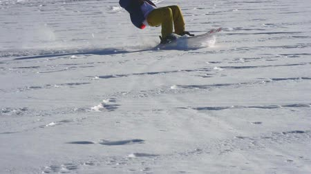 kiting : SLOW MOTION: A male athlete is engaged in kiting on skis. He rolls on the ice of a large lake. Rolling, he performs various jumps, coups and other exercises. The snow flies in different directions from the skis. Windy sunny winter day.