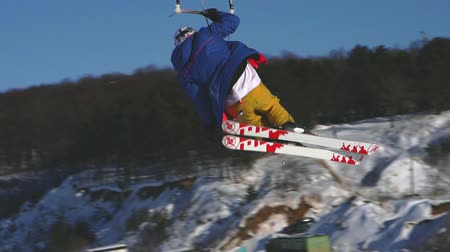 calças : SLOW MOTION: A male athlete is engaged in kiting on skis. He rolls on the ice of a large lake. Rolling, he performs various jumps, coups and other exercises. The snow flies in different directions from the skis. Windy sunny winter day.