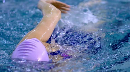 sztafeta : SLOW MOTION: An athlete a woman swims with a style crawl. Female swimmer participating in swimming competitions. She performs beautiful movements with his hands and feet. Splashes of water scatter in different directions