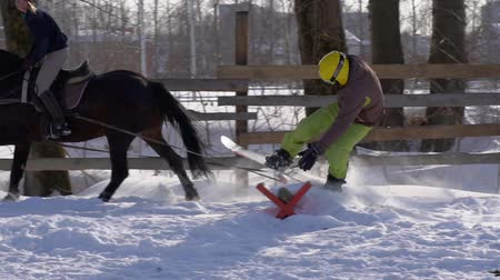 snowbord : SLOW MOTION: A girl galloping on a horse at a gallop. A horse is dragging a snowboarder guy on a rope. A snowboarder rides on a snowboard in snowdrifts. Girl jockey and guy snowboarder work out a jump through the springboard. A sunny winter day. Wideo