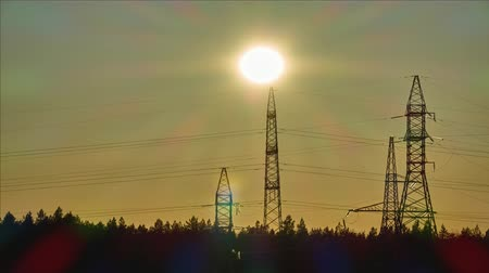 powerline : Sunset over the forest and the pillars of the high-voltage power line. Time lapse.