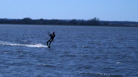 kiting : A male kiteboarder rides on a board along the river. He performs various exercises while moving on water. Water still muddy river, the ice has just melted. Sunny spring day. Stock Footage