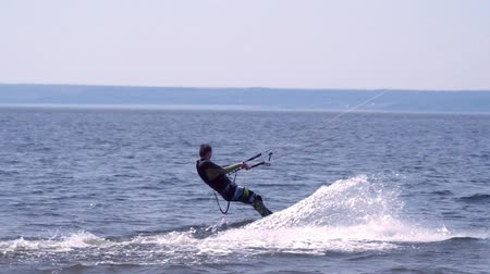 kite boarding : SLOW MOTION: A kiteboarder of male moves beautifully along the waves of a large river. Splashes of water scatter in different directions. Sunny spring day.