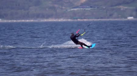 kite boarding : SLOW MOTION:A kiteboarder of male jumps over the surface of the water of a large river. Splashes of water scatter in different directions. Sunny spring day. Stock Footage