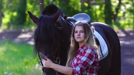 восхитительный : Young blonde woman takes a walk with his horse. A woman caring for a horse. Summer sunny evening. Стоковые видеозаписи