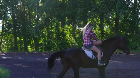 восхитительный : Young blonde woman takes a walk with his horse. A woman is riding a horse. Summer sunny evening.