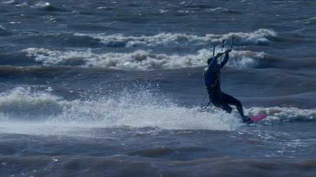 kite boarding : SLOW MOTION: Kiteboarder rides on the board on the waves. Summer sunny evening. Stock Footage