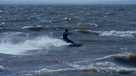 skok : SLOW MOTION: Kiteboarder rides on the board on the waves. Summer sunny evening. Wideo