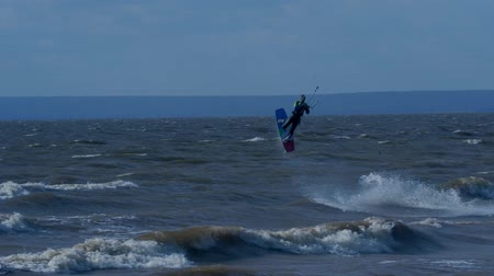 коршун : SLOW MOTION: Kiteboarder rides on the board on the waves. Summer sunny evening. Стоковые видеозаписи