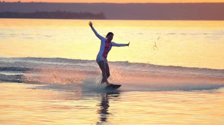 prancha de surfe : SLOW MOTION: A woman is engaged in wakesurfing. She rolls on a board over the smooth surface of the water. Summer sunset.