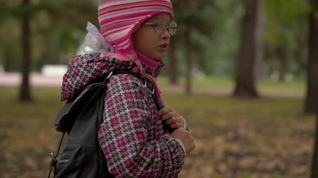 after school : After studying at school. Girl child schoolgirl in glasses goes home on the path of the city park. Slow motion. Stock Footage