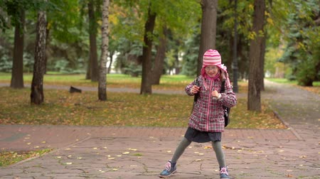 esik : After studying at school. Girl child schoolgirl Minute rest in the park after school. Slow motion. Stock mozgókép