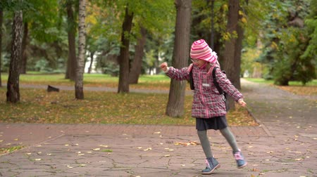 after school : After studying at school. Girl child schoolgirl Minute rest in the park after school. Slow motion. Stock Footage