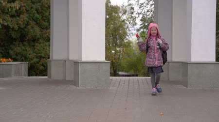 after school : Girl child schoolgirl in glasses goes home after classes. The girl has a good mood. Slow motion. Stock Footage