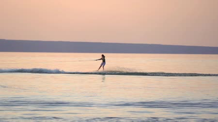 ação : SLOW MOTION: A woman is engaged in wakesurfing. She rolls on a board over the smooth surface of the water. Summer sunset.