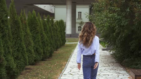 kaštanová : SLOW MOTION: Portrait of a young woman with brown hair. The woman slowly walks along the path of the park.