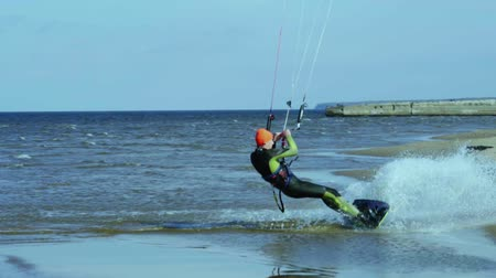 kitesurfer : A male kite surfer rolls on the water.