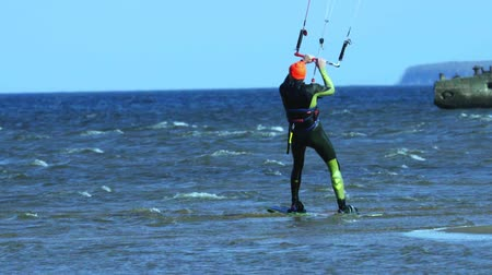 vela : A male kite surfer rolls on the water.