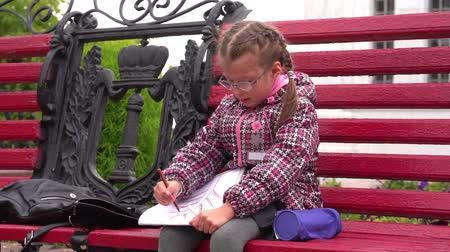 after school : Girl child with glasses A girl sits on a park bench. Autumn day.