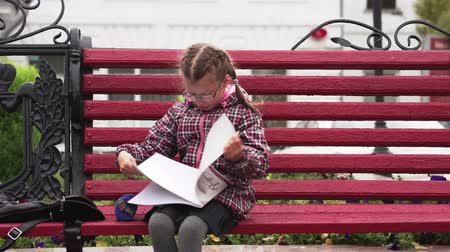 entusiasmo : Girl child with glasses A girl sits on a park bench. Autumn day.