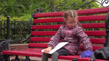 escola : Girl child with glasses A girl sits on a park bench. Autumn day.